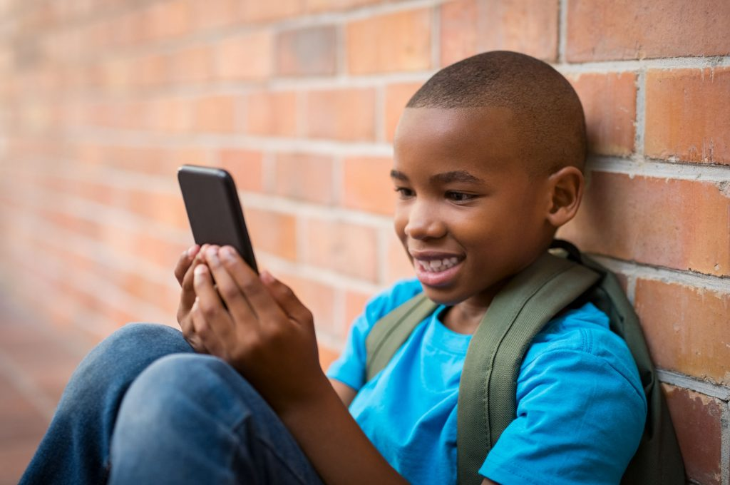 a boy playing educational games on a mobile phone