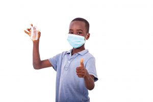 A boy ready for back to school with a mask on and a sanitizer
